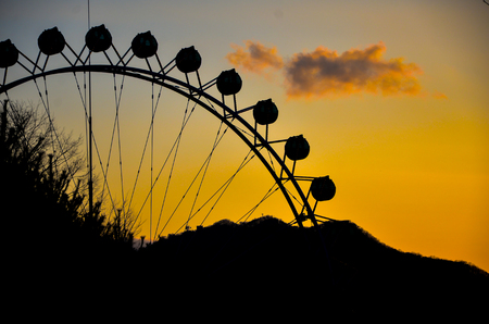 Silhouette of a ferris wheel at sunset. photo