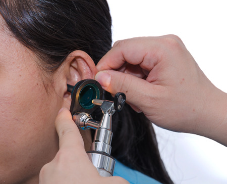ENT physician checking patients ear using otoscope with an instrument. Stock Photo