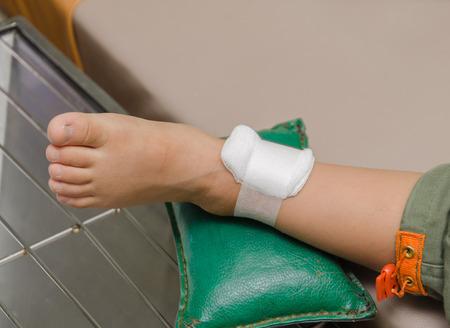 ulceras: ni�o chico con una venda en la pierna y acostado cama de hospital. Foto de archivo