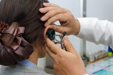 doctor office: ENT physician checking patients ear using otoscope with an instrument. Stock Photo