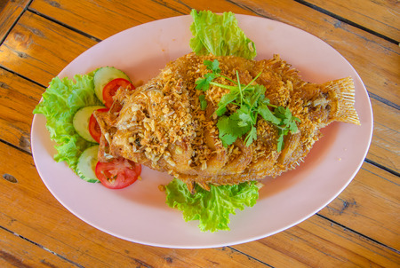 fried tilapia fish with crispy garlic on wood table. photo