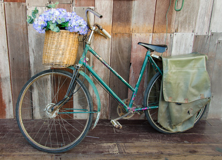parked bicycles: Old ladies bicycle leaning against a wooden plank. Stock Photo