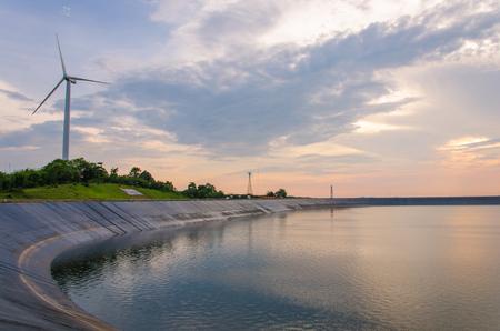 electricity generation: wind turbine generating electricity on dam catchment. Stock Photo