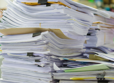 Pile of documents on desk stack up high waiting to be managed. Stock Photo