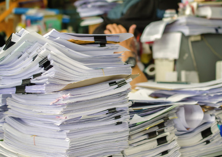 workload: Pile of documents on desk stack up high waiting to be managed. Stock Photo