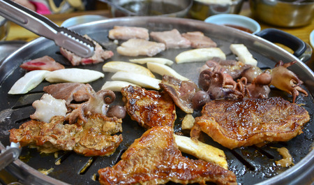 sizzle: Korean barbecue - meat are being cooked on stove.