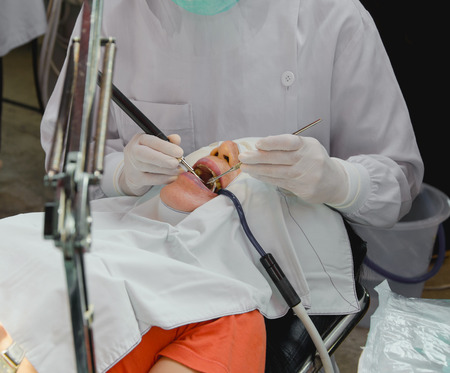 The doctor cleaning the teeth patient with ultrasonic tool