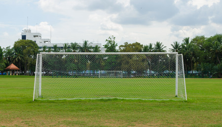 winning pitch: soccer goal at the end of a empty field at a park.