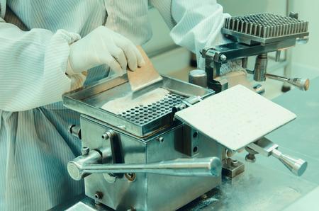 formulation: pharmacist preparing medication with packaging capsule. Stock Photo