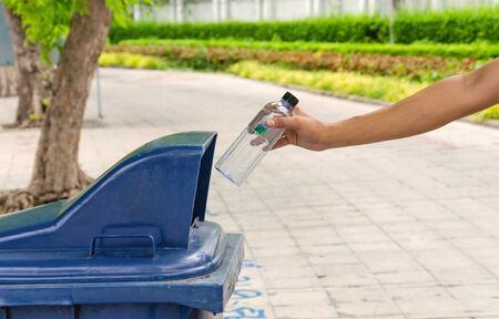 separacion de basura: Mano de lanzar la botella en los botes de basura. Foto de archivo