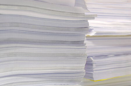 Pile of documents on desk stack up high waiting to be managed photo