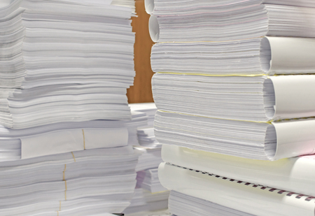 financial management: Pile of documents on desk stack up high waiting to be managed. Stock Photo