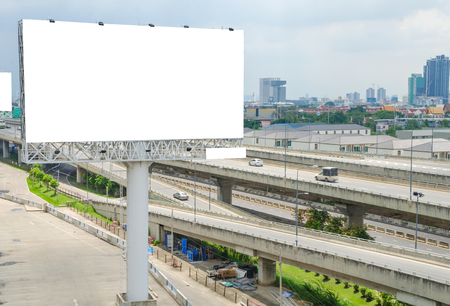 blank billboard: large blank billboard on road with city view background.
