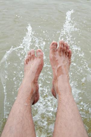 Foot of man in the water splashing.