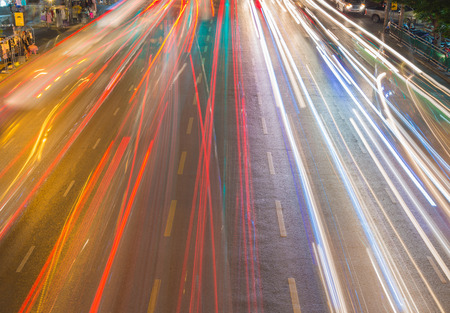 ongoing: light streams from ongoing traffic in business district road. Stock Photo