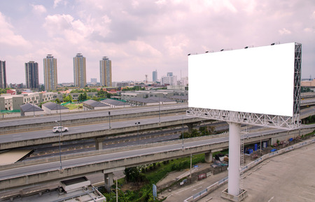 advertising material: large blank billboard on road with city view background.