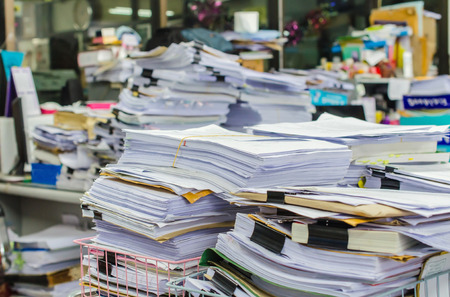 Pile of documents on desk stack up high waiting to be managed. Banco de Imagens