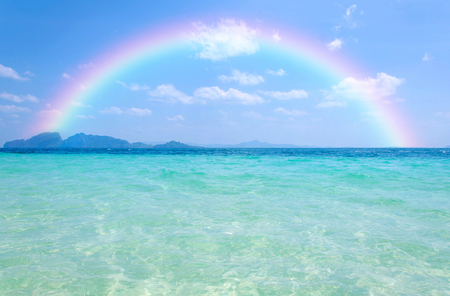 rainbow scene: Colorful rainbow over a Tropical beach of Andaman Sea, Thailand. Stock Photo