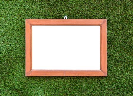 spurious: Empty Wooden photo frame hang on Artificial Green grass background. Stock Photo