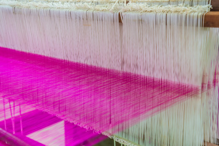 loom: Weaving loom and shuttle on the warp Stock Photo