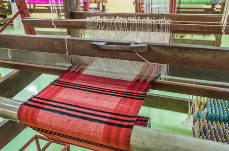 cloth manufacturing: Weaving loom and shuttle on the warp.