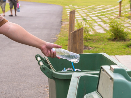 earth pollution: Hand throwing bottle in trash cans.
