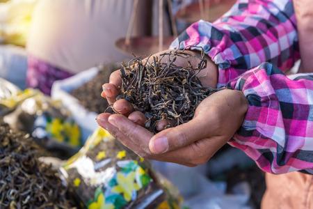 rosas negras: orgánica proceso seco té verde después cogió la mano en el mercado. Foto de archivo