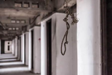 commit: Rope for commit suicide Inside of old abandoned building. (focus at rope)