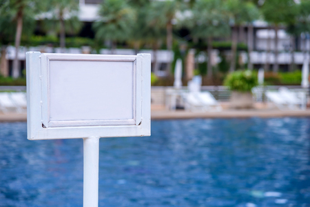 no diving sign: empty of sign standing near a swimming pool.