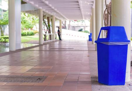botes de basura: trash cans in the park beside the walk way. Foto de archivo