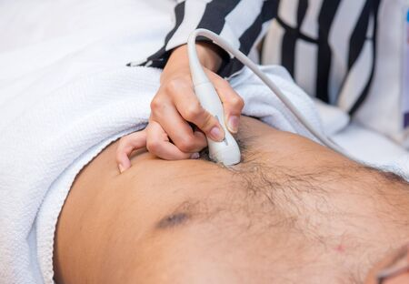 Closeup of man getting an ultrasound scan on abdominal by doctor.