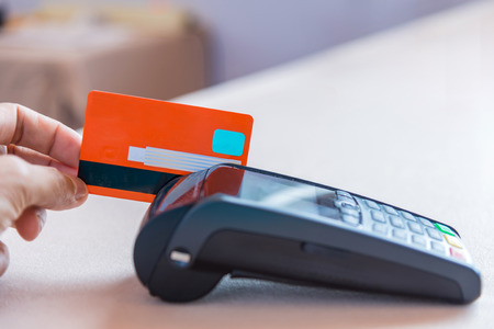 pos: Hand Swiping Credit Card on POS terminal in Store.