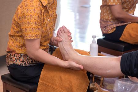 traditional healer: reflexology foot massage in Thai spa treatment.