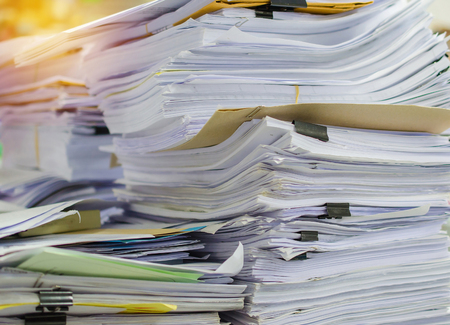 managed: Pile of documents on desk stack up high waiting to be managed. Stock Photo