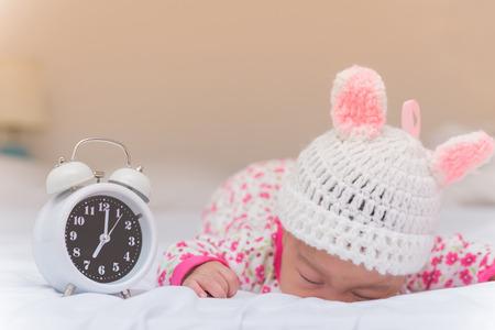 despertarse: niña linda y despertador despiertan por la mañana. Foto de archivo