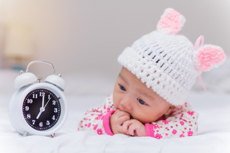 wake up happy: cute baby girl and alarm clock wake up in the morning. Stock Photo