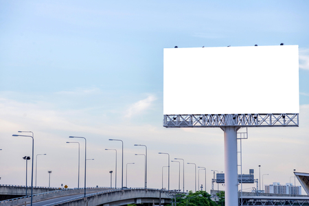 billboard advertising: large blank billboard on road with city view background.