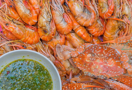 mariscos: Camarones a la parrilla en un plato con salsa de mariscos.