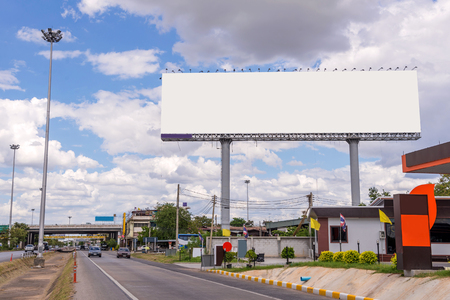 poster: large blank billboard on road with city view background.