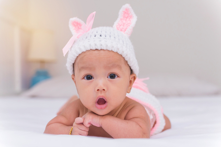 Portrait of cute newborn baby girl on the bed. 스톡 콘텐츠