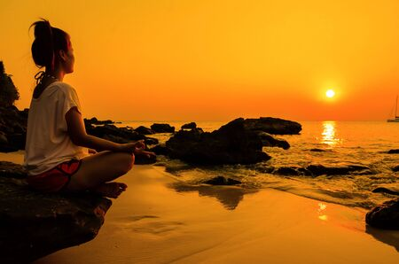 sunset yoga woman with spirituality on sea coast. Foto de archivo