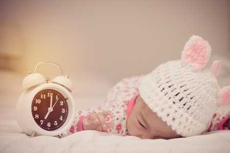 cute baby girl and alarm clock wake up in the morning. Reklamní fotografie
