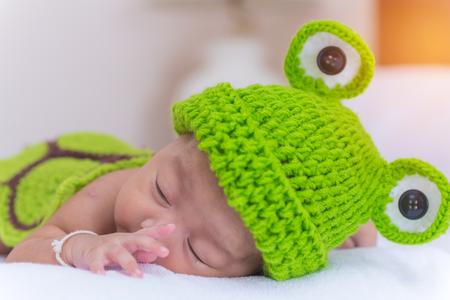 tiny frog: Portrait of newborn baby girl sleep on the bed.
