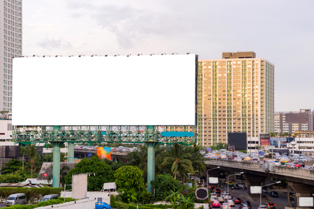 advertising signs: large blank billboard on road with city view background.