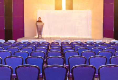 lecture theatre: speaker prepares to lecture but people not interested in listening to lectures.