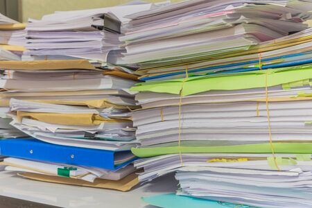 managed: Pile of documents on desk stack up high waiting to be managed