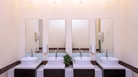 basins: white basins in bathroom interior with granitic tiles.