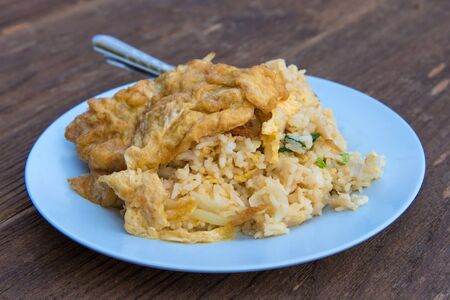 omlet: Pork fried rice with omelet on wood table. Stock Photo
