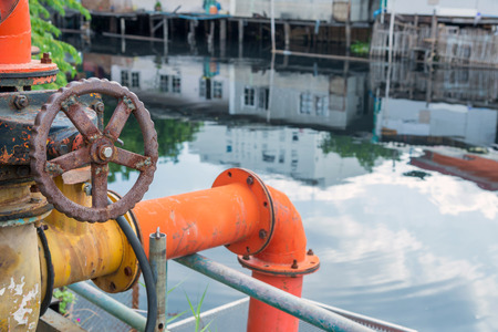 inundated: valve of water pipe for pump system in canal. Stock Photo