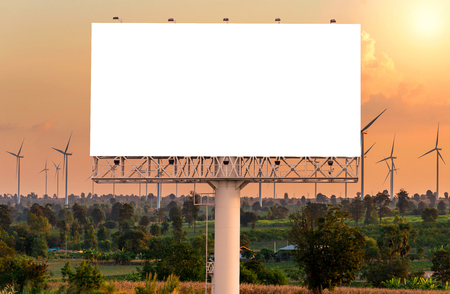 billboard background: Blank billboard for advertisement at Eco power in wind turbine farm with sunset. Stock Photo